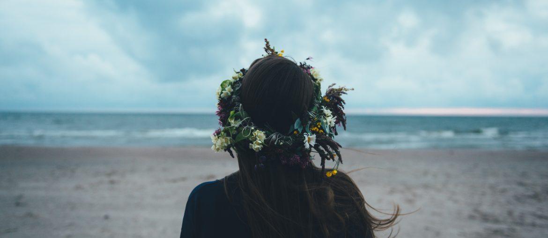 mujer de espaldas sola en la playa con corona de flores
