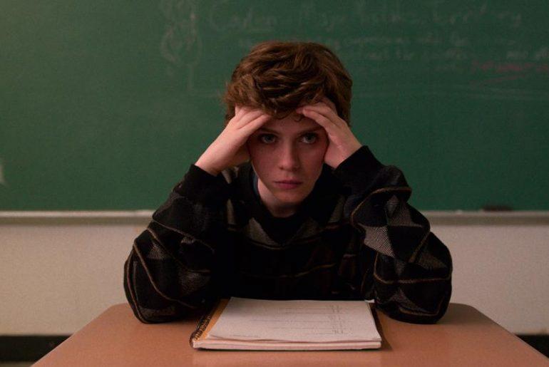 Protagonista de la serie sentada en un pupitre con las manos en la cabeza a modo drama