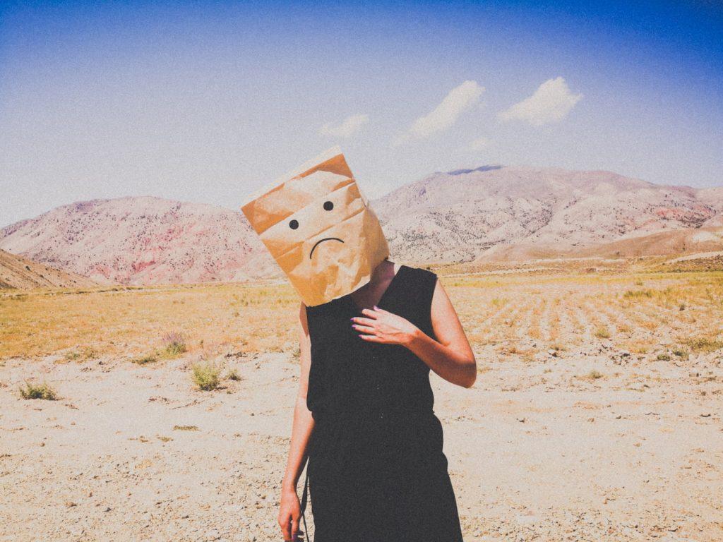 mujer en desierto con bolsa de papel en la cabeza que tiene dibujada una mueca triste